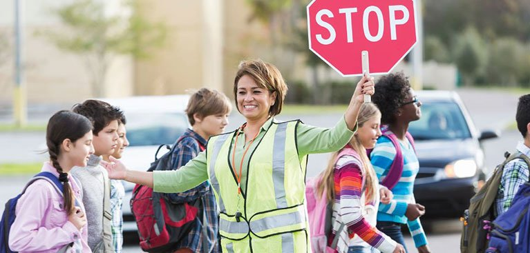 A crossing guard helps school children cross the road.