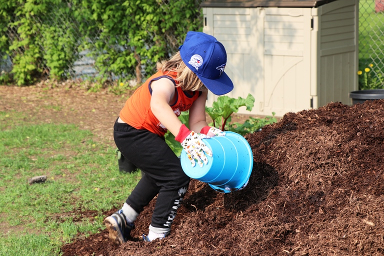 Students and staff were dressed for the sunshine on May 31 and eager to participate in a school-wide planting project.