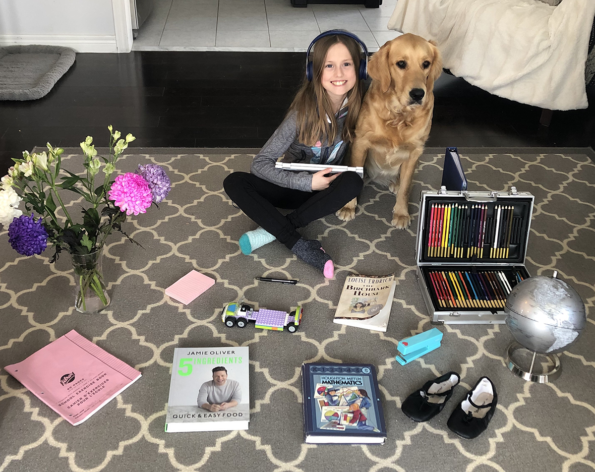 A student and her dog surrounded by art supplies and books.